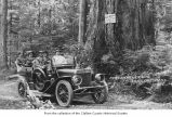 Passenger car, possibly a steam car, on a dirt road carrying passengers between Lake Crescent and...