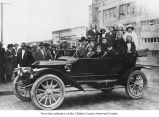 Elmer Day behind the wheel of a passenger car, possibly a steam car, overloaded with young...