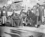 Chinese officials gathered around a table hearing cases and collecting taxes in a Chinese village,...