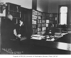 Seattle Public Library interior showing an employee and patron at the periodical room circulation...