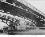 Spokane St. bridge seen from below with workers on the supports, Georgetown neighborhood in...