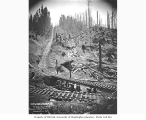 Man standing beside incline railroad tracks, 66 percent grade, Wisconsin Logging and Timber...