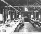 Interior of mess hall with crew member, with suspended condiment shelf above tables, Workman Creek...
