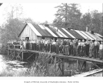Logging and mess hall crews at camp, with raised walkway over pond, Wynooche Timber Company, ca....