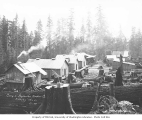 Logging camp no. 4, showing saw filer's shop with windows, bunkhouses, car, and water tank,...