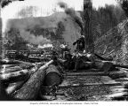 Loggers with donkey engine and logs loaded on skeleton cars, National Lumber and Manufacturing...