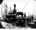 Loggers and donkey engine in National Lumber and Manufacturing Company camp 7, probably in...