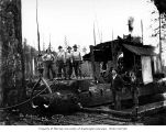Loggers and donkey engine at National Lumber and Manufacturing Company loading site showing...