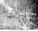 Crew standing on railroad trestle under construction, with pile driver in background,...