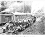 Logging crew on flatbed railroad car at logging camp, Donovan-Corkery Logging Company, ca. 1928