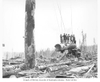 Woman and logging crew members standing on suspended log, with donkey engine in background,...