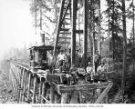 Construction crew with pile driver on railroad trestle under construction, camp 8, Schafer...