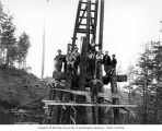 Construction crew with pile driver on railroad trestle under construction, Schafer Brothers...
