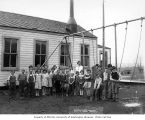 Children and teacher outside of school building, camp 5, Simpson Logging Company, Grays Harbor...