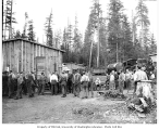 Logging crew at camp, train engine in background, Danaher Lumber Company, ca. 1916