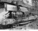 Crew and donkey engine with skids loaded onto railroad skeleton car, Saginaw Timber Company,...