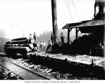 Crew at loading site with donkey engine and railroad skeleton cars, Saginaw Timber Company,...