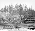 Crew with loaded skeleton car and partially constructed train track, Saginaw Timber Company, near...