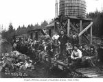 Loggers and a woman sitting on railroad flatcars at logging camp, North Western Lumber Company,...