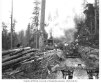 Logging crew, donkey engine, and logging railroad flatbed moving car and tracks, Camp 5, English...