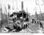 Donkey engine and loading crew, with tongs hanging down in upper right corner, Workman Creek...
