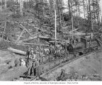 Loggers on railroad car being pushed by Simpson Logging Company's three-truck Shay locomotive 7,...