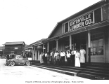 Employees and customers outside Eatonville Lumber Company store and Willard Service Station with...