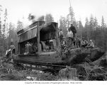 Crew and donkey engines on skids loaded on railroad flatcars, Simpson Logging Company, probably in...