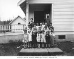 Children and teacher outside of school building, probably at a Simpson Logging Company camp in...