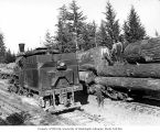 Crew with Donovan-Corkery Logging Company's Climax locomotive 2 beside log train, ca. 1928