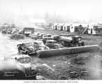 Kosmos Logging Company camp with automobiles, cable cars, and bunkhouses under construction, ca....