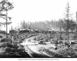 Polson Logging Company's railroad logging camp 14, with cars parked in foreground, near...