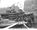 Railroad trestle with Kosmos Logging Company's two-truck Heisler locomotive with crew and tractor...
