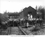 Loggers and mess hall crew at railroad logging camp, with transport car and mess hall in railroad...