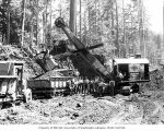 Construction crew with Lima steam shovel and dump trucks with tracks on rear, Polson Logging...