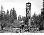 Construction crew with pile driver and railroad trestle under construction, camp 7, Polson Logging...