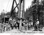 Construction crew and surveyor with pile driver and railroad trestle under construction, camp 7,...