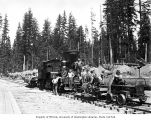 Loggers being transported to work by speeder and on flatcar pulled by Polson Logging Company's...