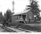 Two men and a woman at logging camp, with speeder on railroad tracks, Coats-Fordney Lumber...