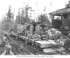 Track gang on speeder with woman watching from beside the track, Greenwood Logging Company, ca....