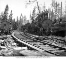 Loggers at railroad logging camp, with locomotive and loaded skeleton cars, Clemons Logging...