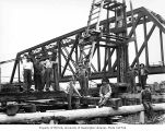 Construction operation with steam-driven pile driver, with metal bridge in background, possibly...
