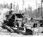 Donkey engine and crew with little girl, Goodyear Logging Company, near Clallam Bay, ca. 1920