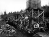 Men and woman on flatcars next to water tank, Northwestern Timber Company, ca. 1915-1945