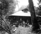 Family group posing outside cottage in woods, Smith Powers Logging Company, Powers, ca. 1922