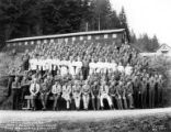 Crew with cooks posing in front of building, Camp Nestucca, Company 5436, Civilian Conservation...