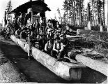 Loggers sitting in dugout canoe which is used for transportation to and from work, unidentified...