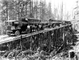 Four Garford logging trucks carrying loads on temporary trestle, Washington, n.d.