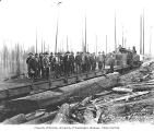 Logging crew standing on flatcar, with Mud Bay Logging Company's Baldwin 2-6-2TT locomotive no. 3,...