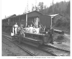 Mess hall crew at railroad camp, standing on speeder, Mason County Logging Company, ca. 1932